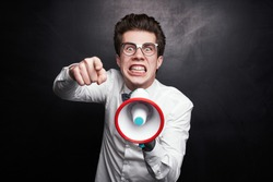 Man nerd in glasses pointing at camera and speaking in megaphone accusingly against black background