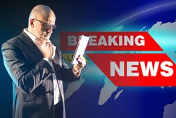 Man next to breaking news. Concept - presenter getting ready for broadcast. Concept - work of a journalist. Reporter is getting ready for release. Adult man holds a tablet. News presenter career.