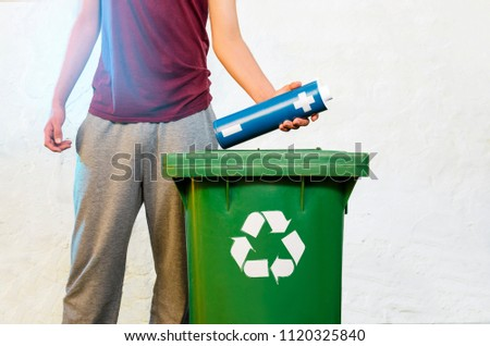 Man no face, throwing enlarged AA battery in recycle bin, toxic waste, e waste concept