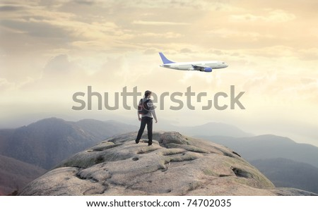 Man observing an airplane from a rock