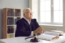 Man of law and justice. Serious, honest and wise old judge sitting at table in court. Fair incorruptible mature lawyer sitting at desk with gavel and open Code of Law in his office or courtroom