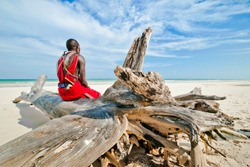 man of the Maasai tribe sits on the shore of the Indian ocean