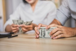 Man offering batch of hundred dollar bills. Hands close up. Venality, bribe, corruption concept. Hand giving money - United States Dollars (or USD). man counting money at the table.