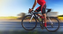 Man on a bicycle on a road with motion blur of truck on highway at morning light