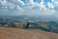 Man on a hang glider preparing to jump from mountain, green valley and small town in the background