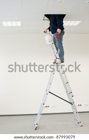 man on a ladder with a hydraulic wrench , looks over the ceiling