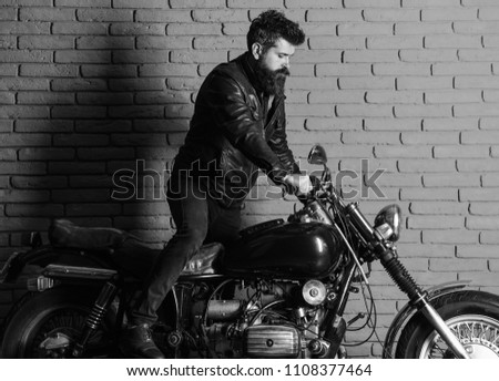 man on a motorcycle. Hipster, brutal biker on serious face in leather jacket gets on motorcycle. Man with beard, biker in leather jacket near motor bike in garage, brick wall background #1108377464