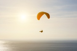 Man on a paraglider, silhouette, flight over the sea
