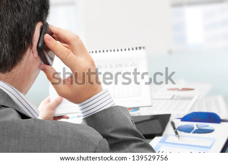 Man on a Phone Analyzing Financial Data and Charts in the Office