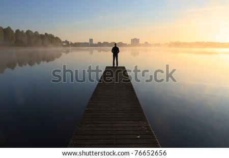 Man on a pier looking toward the city over a foggy lake during sunrise.