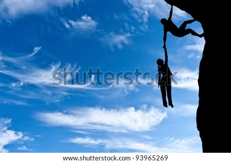 man on a rock holding the hand of a woman dangling over the precipice in the sky