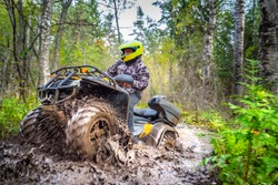 Man on ATV rides on a dirt road. Powerful transport. Off-road trip. Extreme rest. A trip through the autumn forest. Racing in nature.