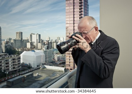 Man on balcony with camera - stock photo
