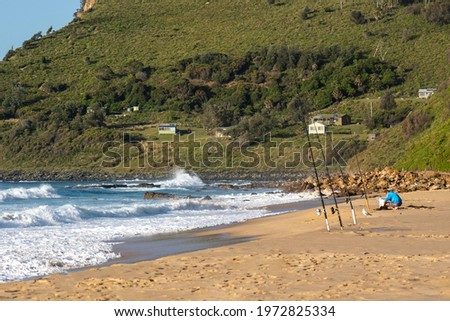 man on beach preparing setting up fishing rode to catch some fish Stock fotó ©