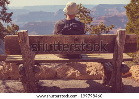 man on bench in grand canyon ...