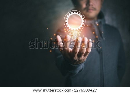 man on blurred background holding virtual screen lightbulb with a cog.new idea creative idea.Concept of idea and innovation. #1276509427