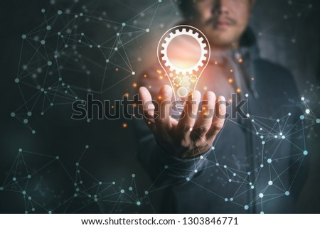man on blurred background holding virtual screen lightbulb with a cog.new idea creative idea.Concept of idea and innovation. #1303846771