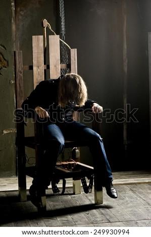 Man on electric chair. Dramatic studio lighting