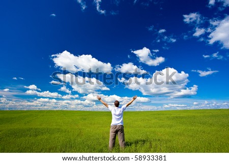 man on field rising up hands