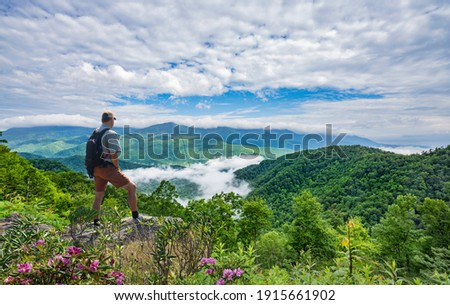Man on hiking trip, standing on top of the mountain over the clouds, enjoying beautiful summer mountain scenery. Hiker looking at beautiful view. Blue Ridge Mountains, North Carolina, USA. Stock photo ©