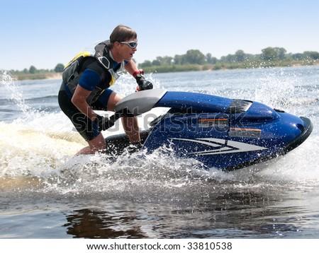 Man on jet ski rides very close - stock photo