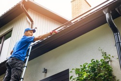 man on ladder cleaning house gutter from leaves and dirt