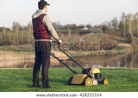 Man on lawn mower cuts the lake. #428255554