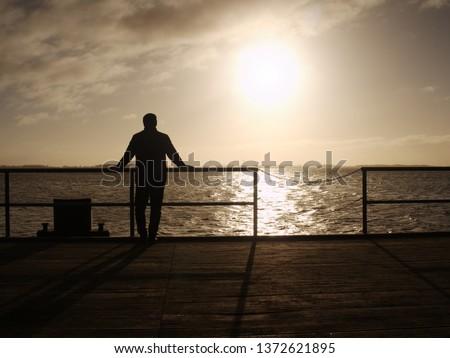 Man on long touristic mole within autumn misty morning. Tourist at handrail. #1372621895