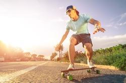 Man on longboard skate at sunset
