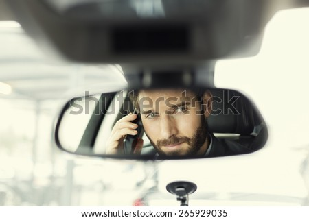 Man on mobile phone in the car. Reflection in the mirror