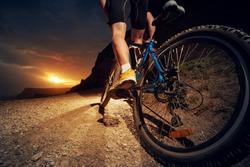 Man on mountain bike rides on the trail on a beautiful sunset. Bicycle wheel closeup.