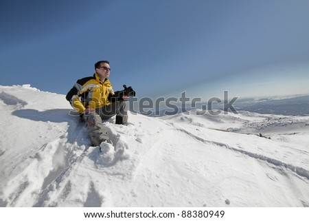 Man on mountain with camera - stock photo