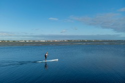 Man on Paddle Board at Costa Nova bay in Portugal gliding smoothly on calm blue waters on a late afternoon. Relaxed, calm and alone, one with nature in Portugal surrounded by rich blue tones.