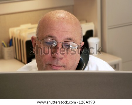 Man on phone looking over monitor
