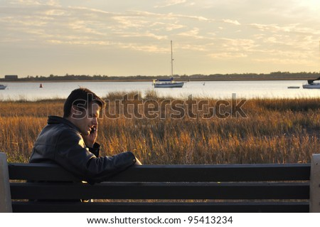 Man on phone sits on bench by bay