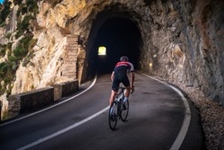 Man on road bicycle ride on the road in mountains. Dark rocky tunnel on the Road. Sa Calobra, Majorca, Spain