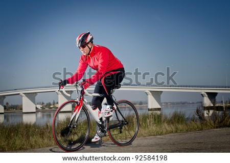 Man on road bike riding down open country road, bridge on background.