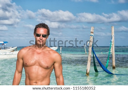 Man on sea beach in costa maya, mexico. Sexy man with muscular torso enjoy sunny day on caribbean beach. Man sunbathing and relax on beach. Summer beach vacation for muscular man. Ready to have fun.