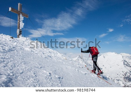 Man on ski reaching the summit in the Alps