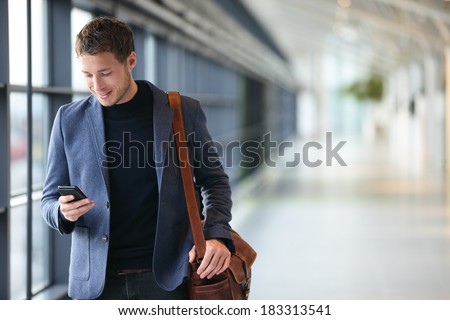 Man on smart phone - young business man in airport. Casual urban professional businessman using smartphone smiling happy inside office building or airport. Handsome man wearing suit jacket indoors.