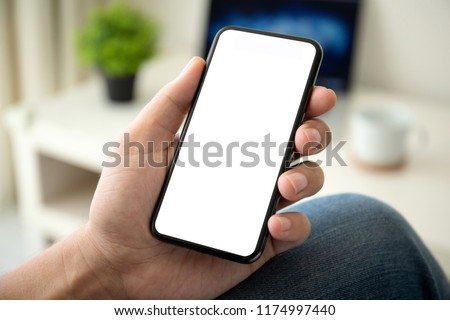 man on sofa holding phone with isolated screen in the room of house