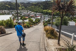 Man on the Baldwin Street world s steepest street in Dunedin, Otago, New Zealand.