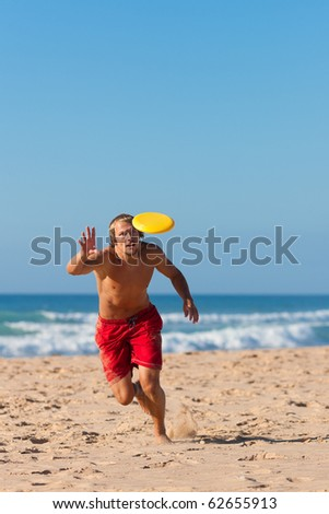 Man on the beach playing frisbee