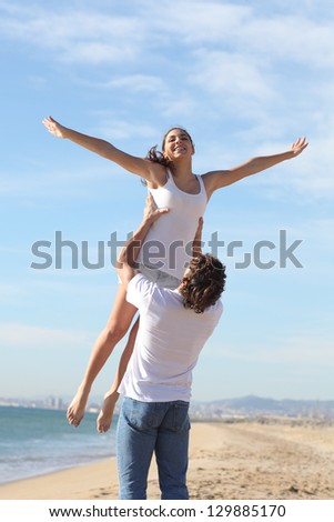 Man on the beach raising his beautiful girlfriend