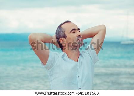 man on the beach taking deep breath enjoying fresh air freedom