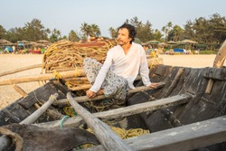 Man on the beach. Traveler sits in traditionaI Indian fishing boat at sunset and looks out to sea. The lifestyle people. A male in traditional Indian white clothing poses in sunset rays and enjoys.