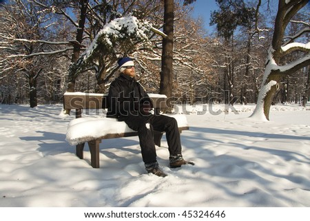 Man on the bench in winter day - park.