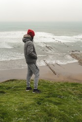 Man on the cloudy shore looking at the sea on the grass