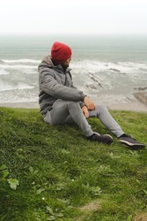Man on the cloudy shore sitting looking at the sea on the grass