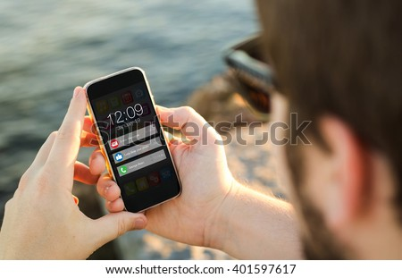 man on the coast looking at notifications on his smartphone. All screen graphics are made up.